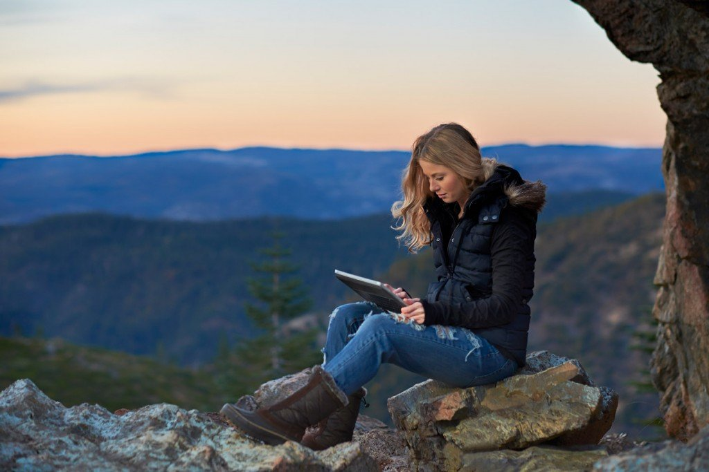 A young woman reading a book on a tablet high in the Sierra Nevada Mountains of Northern California.