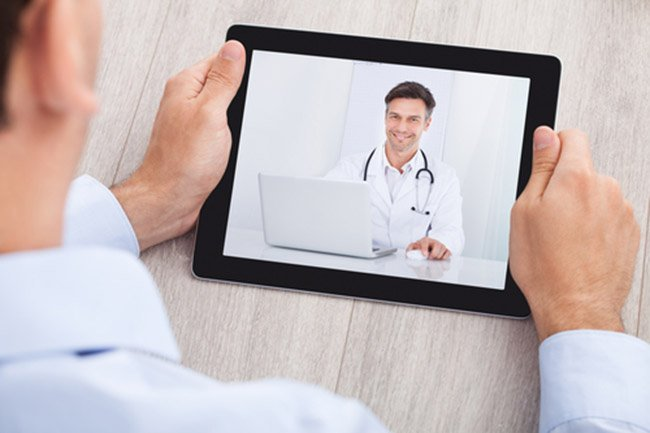 Cropped image of businessman video conferencing with doctor on digital tablet at desk in office
